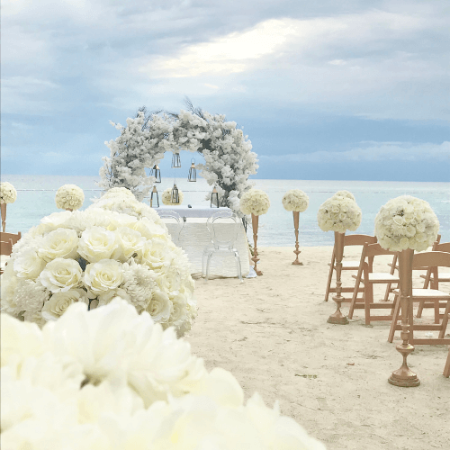 altar on a beach with flowers and chairs for the guests