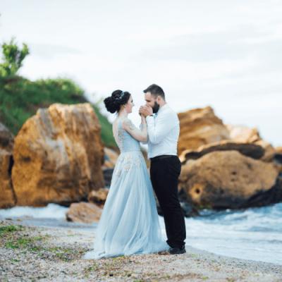 couple on the beach near rocks